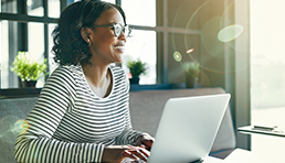 Image of woman doing work on a laptop illustrating that hybrid and multicloud solutions enable unique workload delivery from anywhere